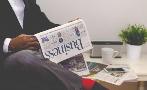 Um homem sentado lendo um jornal de negócios